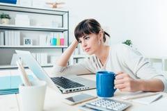 Mujer cansada en el escritorio de oficina imagenes de archivo