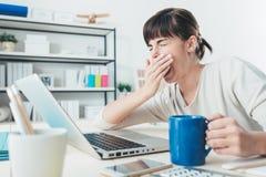 Mujer cansada en el escritorio de oficina foto de archivo