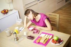 Mujer cansada en los pijamas que desayunan en el país Imagen de archivo libre de regalías