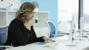 Mujer cansada joven en los vidrios que se sientan en el ordenador portátil mientras que trabaja en la oficina, después casi caer  almacen de video