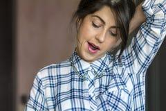Mujer cansada joven que bosteza Foto de archivo