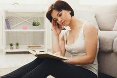 Mujer cansada joven que lee un libro Fotos de archivo