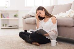 Mujer cansada joven que lee un libro Foto de archivo