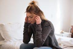 Mujer cansada joven triste que se sienta en la cama Fotografía de archivo