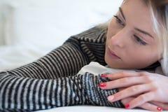 Mujer cansada joven triste que se sienta en la cama Imagenes de archivo