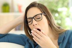 Mujer cansada que bosteza en casa Fotografía de archivo