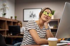 Mujer cansada que cubre ojos con el post-it imágenes de archivo libres de regalías