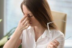 Mujer cansada que da masajes al puente de la nariz, dolor de cabeza de sensación de la fatiga visual, imagen de archivo