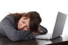 Mujer cansada que duerme con la computadora portátil Foto de archivo libre de regalías