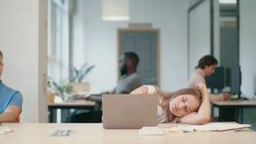 Mujer cansada que duerme en el lugar de trabajo Señora soñolienta que pone en la tabla con el cuaderno almacen de video