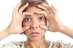 Mujer cansada que la abre ojos con los fingeres Fotografía de archivo