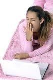 Mujer cansada que mira al revés con la computadora portátil Fotos de archivo