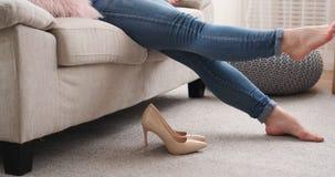 Mujer cansada que quita stilettoes y que se relaja en el sofá almacen de metraje de vídeo