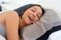 Mujer cansada que ronca en alta voz en la cama foto de archivo
