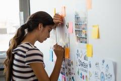 Mujer cansada que se inclina en la pared con las notas pegajosas en oficina Fotos de archivo libres de regalías
