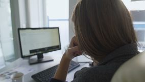 Mujer cansada que se sienta en la documentación de la lectura de la oficina y para el extremo del día que espera metrajes
