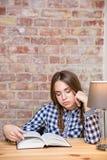 Mujer cansada que se sienta en la tabla con el libro en casa Imagenes de archivo