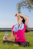 Mujer cansada que se sienta en parque con la toalla y la botella Imagenes de archivo