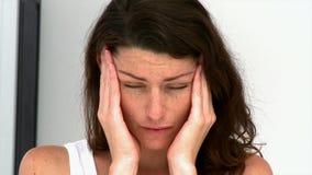 Mujer cansada que tiene un dolor de cabeza almacen de metraje de vídeo
