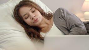 Mujer cansada que trabaja en el ordenador portátil en dormitorio La mujer triste despierta en cama metrajes