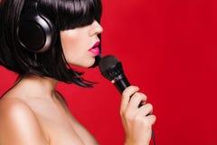 Mujer cantante hermosa con el micrófono cantante Imagen de archivo libre de regalías