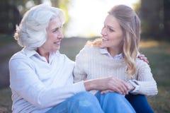 Mujer cariñosa que disfruta de la conversación con la madre mayor en el parque Foto de archivo