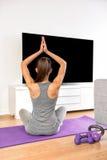 Mujer casera de la aptitud que hace el ejercicio de la yoga que ve la TV Imagen de archivo libre de regalías