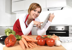 Mujer casera feliz del cocinero en delantal en la cocina usando la tableta digital como libro de cocina Imágenes de archivo libres de regalías