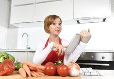 Mujer casera feliz del cocinero en delantal en la cocina usando la tableta digital como libro de cocina foto de archivo libre de regalías