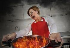 Mujer casera inexperta joven del cocinero en pánico con el delantal que sostiene el pote que quema en llamas con en pánico Fotos de archivo