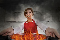 Mujer casera inexperta joven del cocinero en pánico con el delantal que sostiene el pote que quema en llamas con en pánico Imagen de archivo