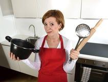 Mujer casera novata del cocinero en la cocina roja del delantal en casa que celebra cocinar la cacerola y el rodillo tristes en l Foto de archivo libre de regalías
