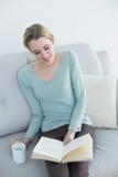 Mujer casual alegre que lee un libro que sostiene una taza Foto de archivo libre de regalías
