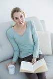 Mujer casual atractiva que se sienta en el sofá mientras que lee un libro Foto de archivo libre de regalías