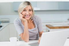 Mujer casual con café y el ordenador portátil en cocina Imagenes de archivo