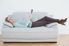Mujer casual contenta que sostiene el periódico que miente en el sofá Imágenes de archivo libres de regalías