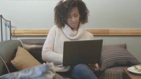 Mujer casual del estudiante que se sienta en la cafetería y que usa el ordenador portátil almacen de video