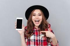Mujer casual emocionada que señala el finger en el teléfono móvil de la pantalla en blanco Imagen de archivo libre de regalías