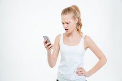 Mujer casual enojada que usa smartphone Imagen de archivo libre de regalías