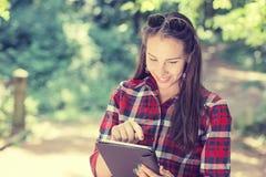 Mujer casual feliz atractiva que usa la PC del móvil del cojín imagen de archivo