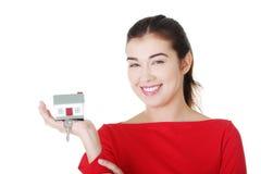 Mujer casual feliz que lleva a cabo las teclas HOME. Imágenes de archivo libres de regalías
