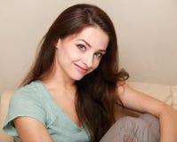 Mujer casual feliz que se sienta en el sofá Foto de archivo