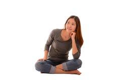 Mujer casual feliz que se sienta y que piensa en el fondo blanco Co Foto de archivo