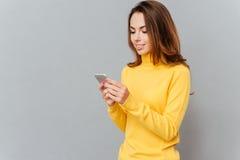 Mujer casual feliz que usa smartphone Fotografía de archivo libre de regalías