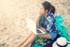 Mujer casual hermosa con un ordenador portátil en la playa Fotografía de archivo libre de regalías