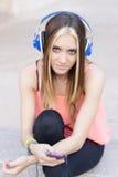 Mujer casual hermosa que escucha la música con los auriculares y el pH Imagen de archivo
