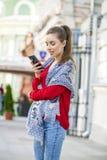 Mujer casual hermosa que manda un SMS en su teléfono celular Imágenes de archivo libres de regalías