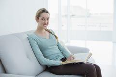 Mujer casual hermosa que se sienta en el sofá que lee un libro Imagen de archivo libre de regalías