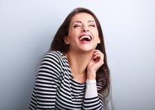 Mujer casual joven de risa con la boca abierta de par en par y los ojos cerrados Fotos de archivo