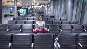 Mujer casual joven hermosa que hace la meditación de la yoga en un terminal de aeropuerto vacío almacen de video